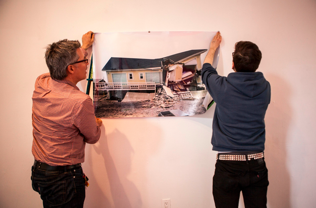 Anthony Aziz, left, the director of the BFA Fine Arts program at Parsons, helps student Robert Hickerson hang a piece for the benefit show. Photo: Natalie Keyssar for The Wall Street Journal
