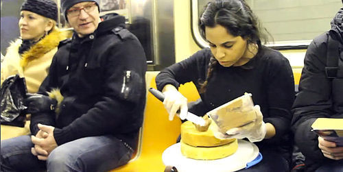 Banayan ices a two-layer cake on the train as fellow commuters look on. Still from video by Vanessa Turi (Parsons BFA Fine Art '13)